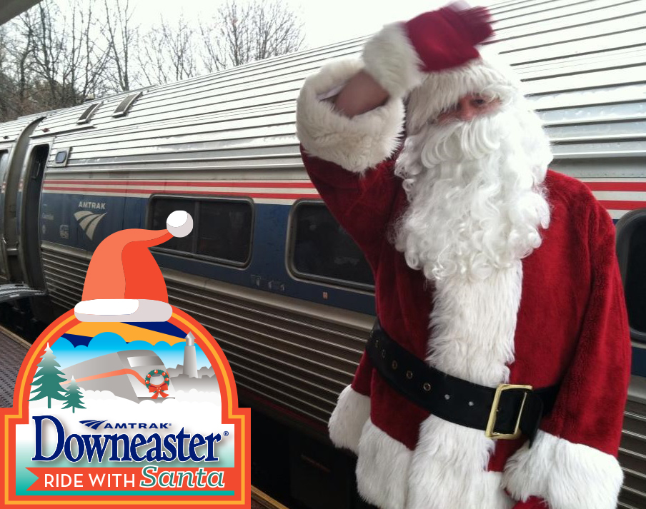 Santa waves while standing next to train