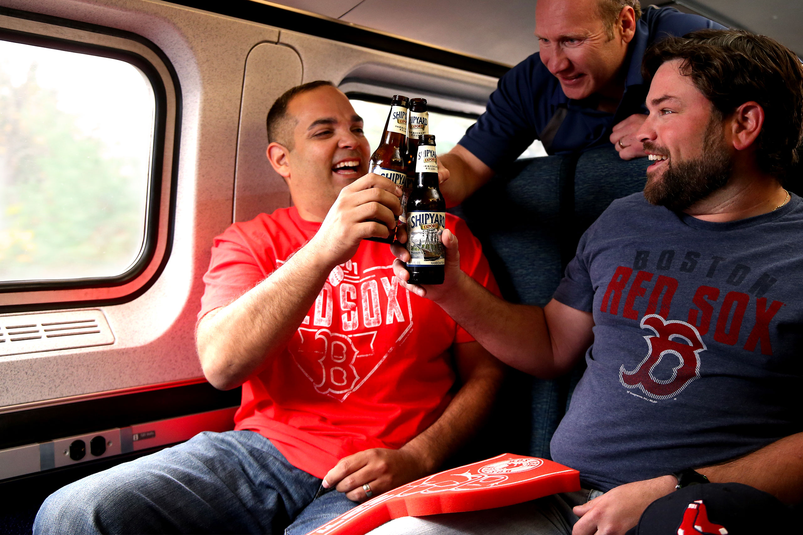 Three men in Red Sox shirts smile and clink bottles together on train.