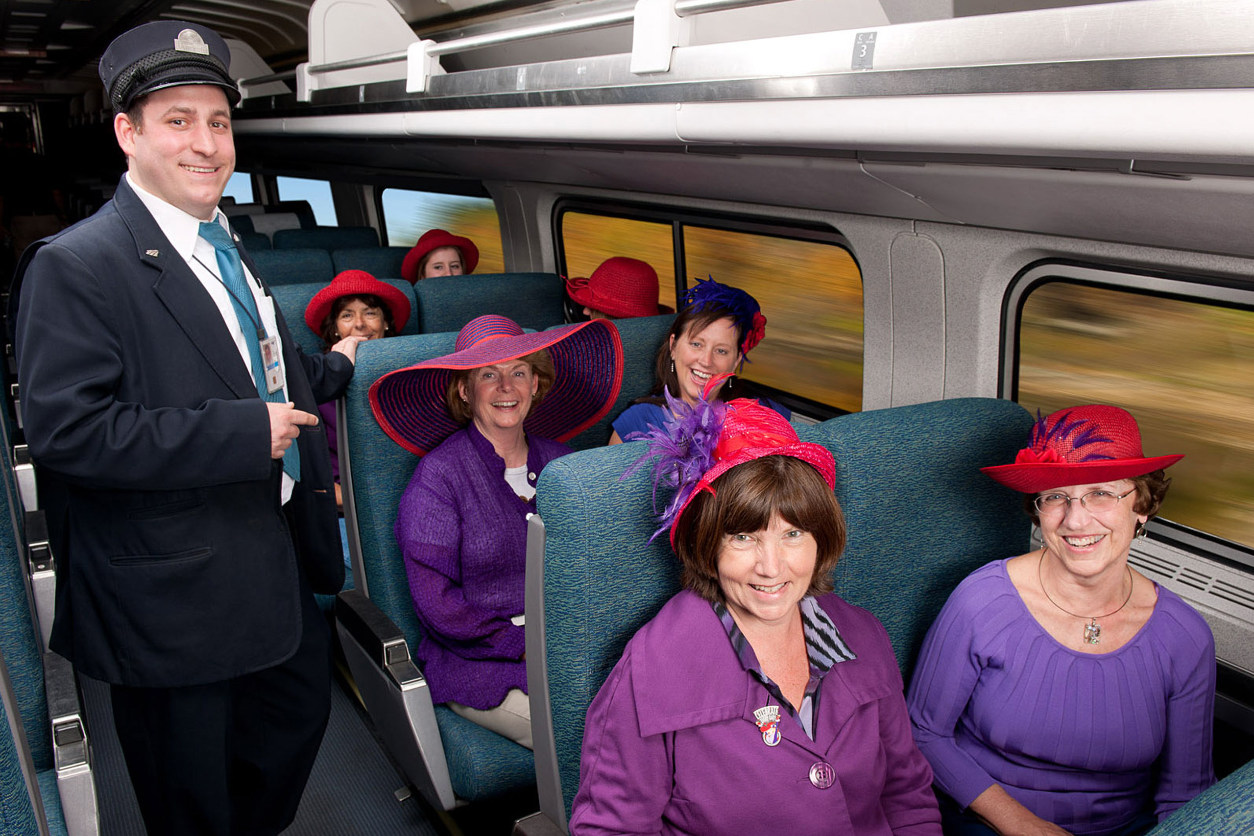 Women with matching clothing and hats ride train