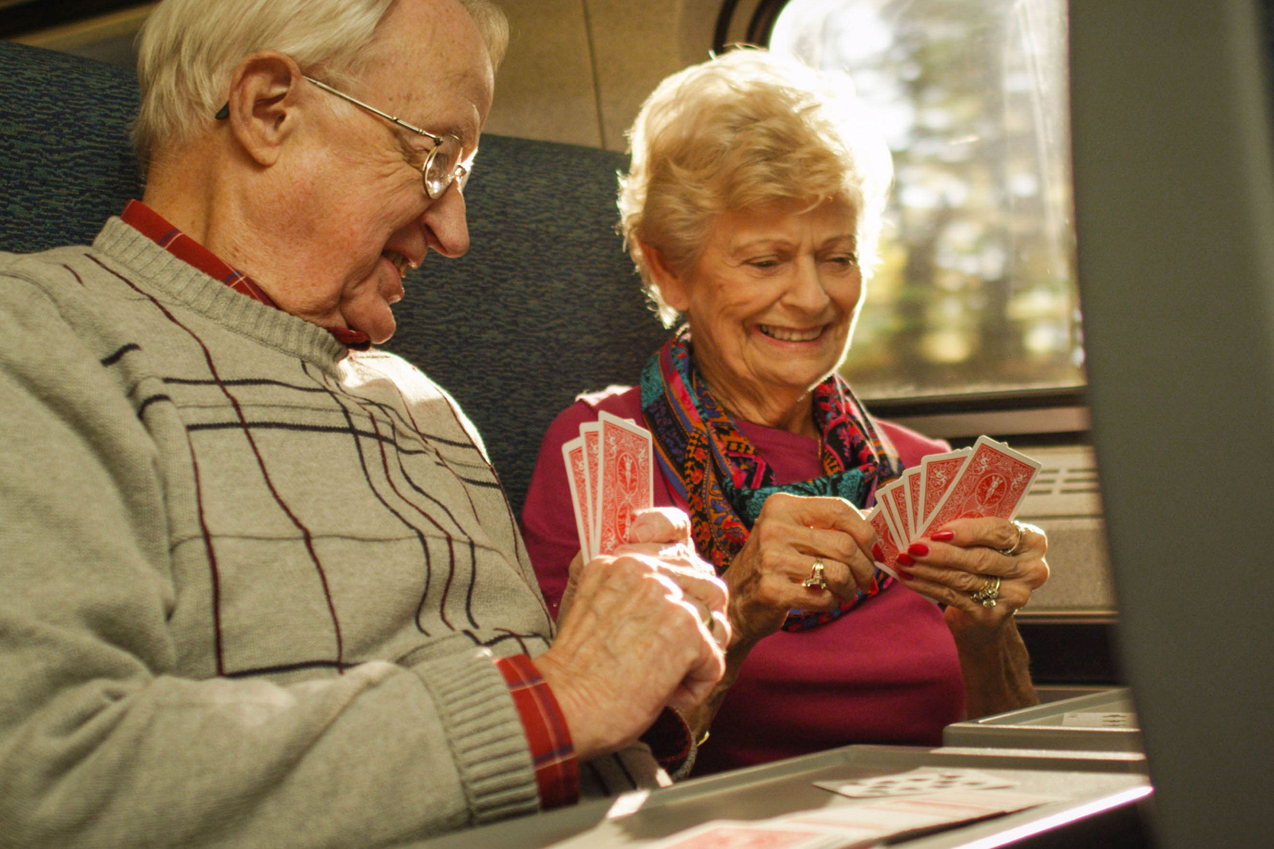 Senior couple smile and play cards on train.