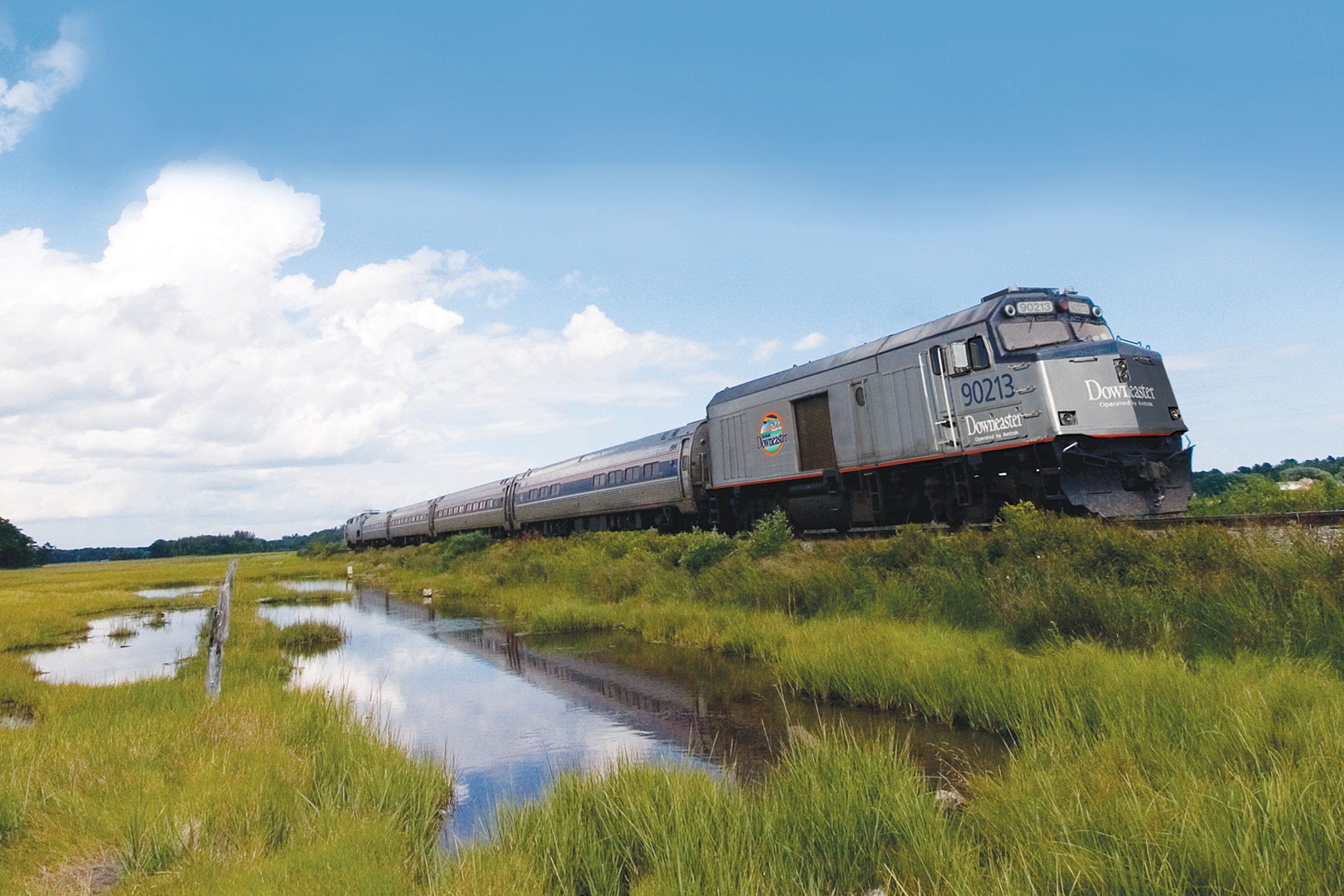 Downeaster train travels through wetlands on sunny day