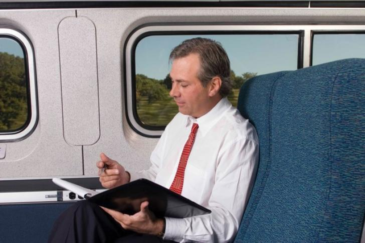 Business man rides train and works on tablet