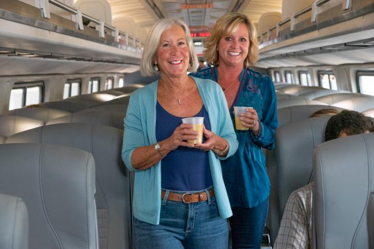 Women walking on train and enjoying a beverage.
