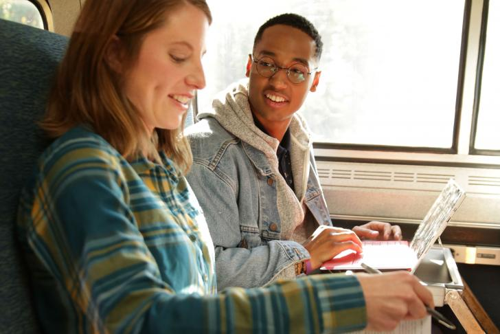 College students converse on train