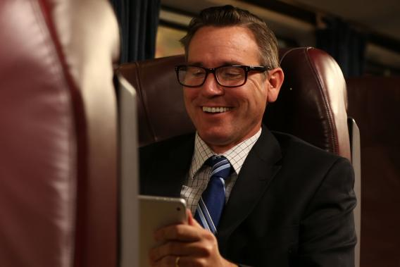 Man in business suit smiles and looks at tablet.