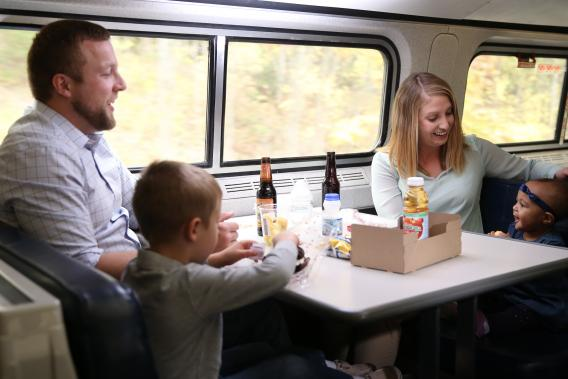 Young family smiles and enjoys food and drink on café car.