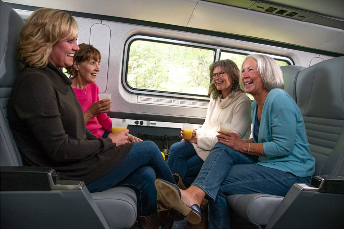 Women laugh and enjoy drinks on train