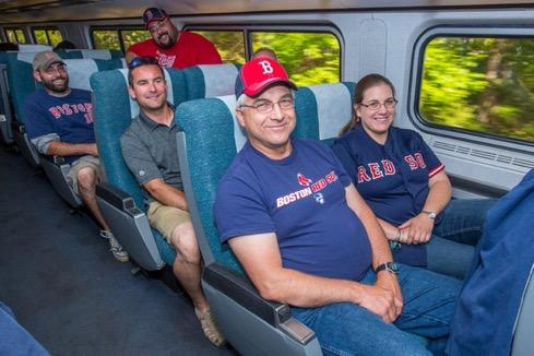 Family wearing Red Sox clothes rides train smiling