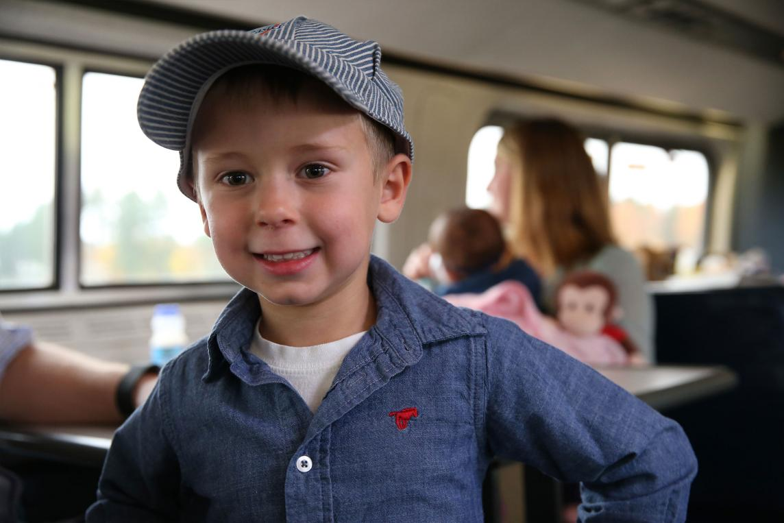 Smiling child with hat rides train
